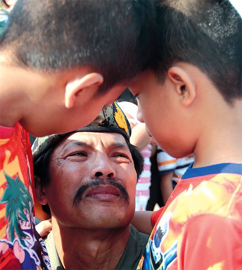 Chief Petty Officer 1st Class Boonsueb Utako is close to tears as he is greeted by his two sons after returning to Thailand yesterday following the anti-piracy mission in the Gulf of Aden off Somalia. PHOTOS BY JETJARAS NA RANONG.