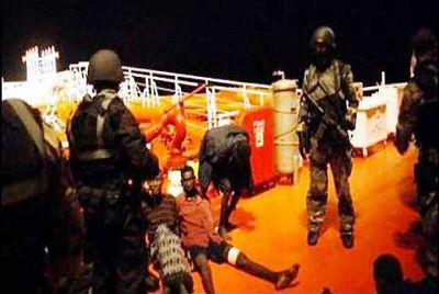 Under control: The commandos watching over the Somali pirates.