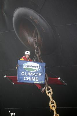 Greenpeace activist Drew Hahn hangs off the anchor chain of the Great Motion.