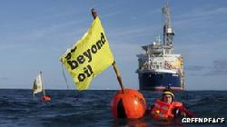 Greenpeace protesters swim in front of oil ship
