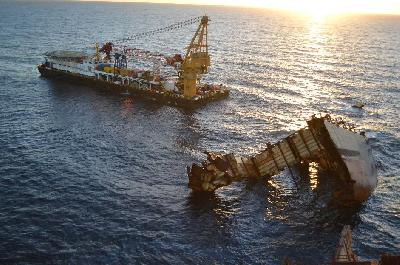 The crane barge Smit Borneo is positioned on the starboard side of the wreck.