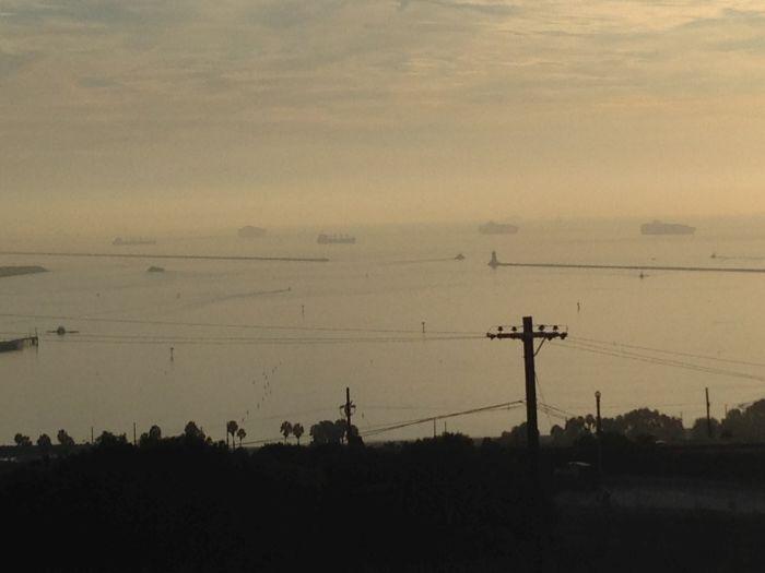 Fourteen ships at anchor at LA-Long Beach, 2 boxships less than day before